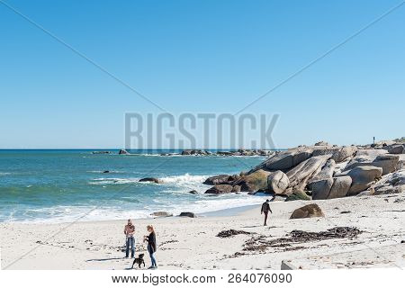 Cape Town, South Africa, August 9, 2018: People And A Dog On A Beach In Camps Bay In Cape Town In Th