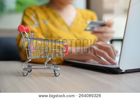 Close Up Mini Shopping Cart, Asian Woman Holding Credit Card And Using Laptop For Online Shopping Wh