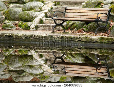 Park Bench Reflection In A Tranquil Scene