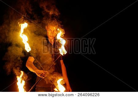 Fire Show. The Fakir Juggles With Two Staff. Night Performance. Fire And Smoke. Fascinating Flame Mo