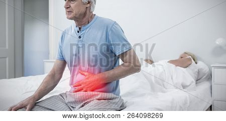 Highlighted pain against senior man having stomach pain while sitting on bed