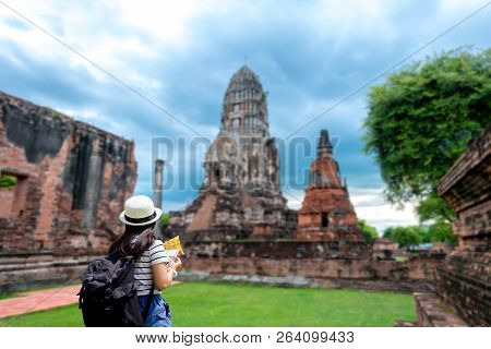 Tourist Women With Carrying A Backpack Viewing Poster, About The Temple In Ayutthaya At  Ratchaburan