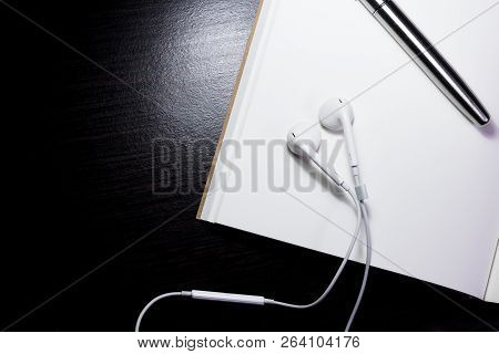 Image Is Top View.open Note Paper And Pen Color Gray With White Earphone And Wood Desk Background.