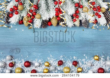 Christmas Background With Snowy Fir Tree And Colorful Holiday Balls On Blue Wooden Table Top View. G