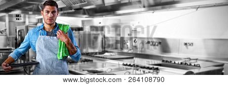 Male waiter holding tray against picture of restaurant kitchen