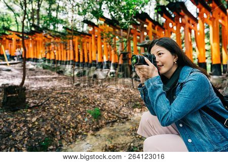 Asian Photographer Crouching Near The Red Gate