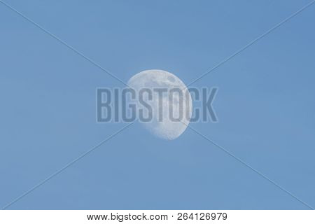 Rising Moon During The Daylight On The Blue Sky