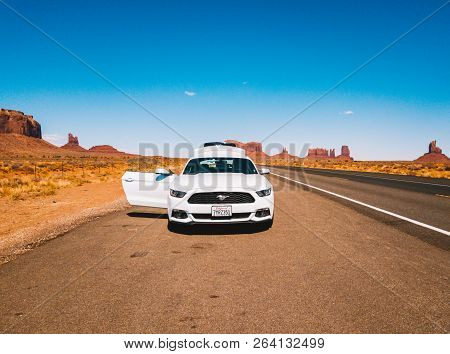 July 30, 2018. Monument Valley National Park, Utah, Usa. White Ford Mustang Parked By The Side Of Th