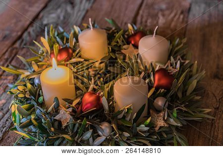 Traditional Advent Candles Wreath With Ornaments And One Burning Candle On Wood, First Advent