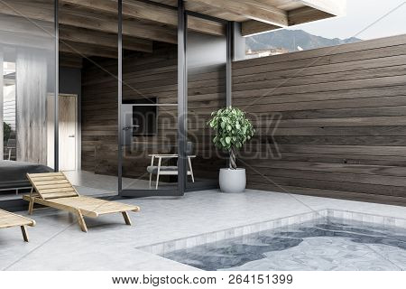 Two Deck Chairs Standing Near Private Pool. Master Bedroom With Gray Bed In The Background. Dark Woo