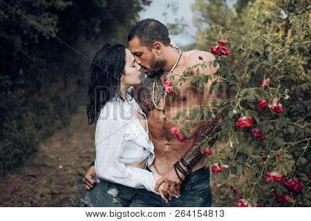 Sensual Couple Kissing In Flowers Garden. Young Lovers In Romantic Moments. Feeling And Emotion Conc