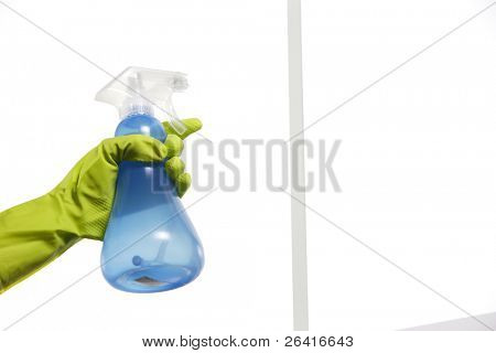 Spraying window cleaner on the glass with a spray bottle and gloves