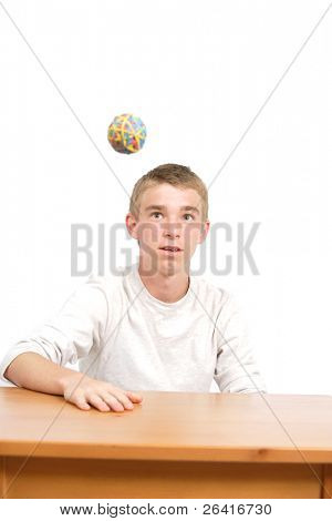 A teen age student playing with a rubber band ball in class