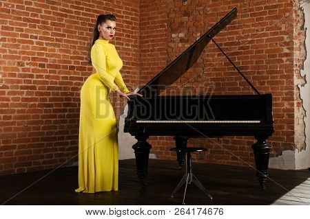 Beautiful Sensual And Sexy Blonde Girl In A Yellow Dress Standing Near The Piano Against A Brick Wal