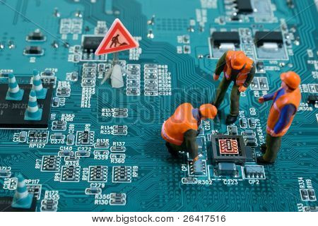 Miniature Engineers Fixing Error On Chip Of Motherboard