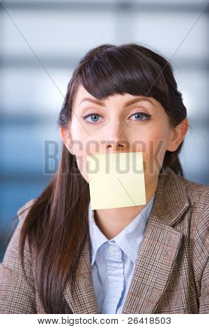 Business woman with blank post it over mouth