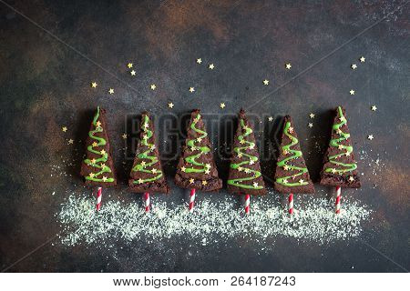 Chocolate Brownie In Shape Of Christmas Tree With Green Icing And Festive Sprinkles, Top View, Copy