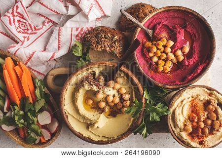 Different Hummus Bowls. Chickpea Hummus, Avocado Hummus And Beet Hummus. Plant Based Diet Food.