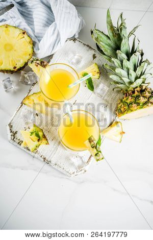 Fresh Pineapple Juice Or Cocktail, With Pieces Of Fresh Pineapple, Ice, Decorated With Mint, On A Wh