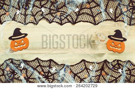 Halloween background. Black cobweb lace border and Halloween decorations on the wooden background with free space for Halloween holiday text