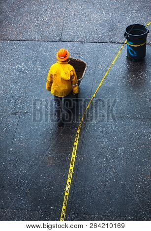 New York, Usa - May 03, 2016: Construction Worker In A Yellow Protective Cloak Pushing A Wheelbarrow