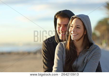 Happy Couple Of Teens Looking At Horizon At Sunset On The Beach