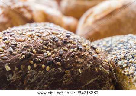 Close-up of Mixed Bread and baked Bread rolls usable as decorative Food Background. Freshly baked Whole-grain Bread Rolls with different Seeds.