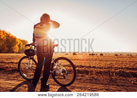 Middle-aged woman bicyclist riding in autumn field at sunset. Senior sportswoman admiring the view. poster