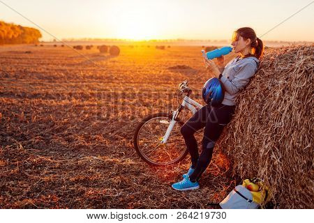 Young bicyclist having rest after a ride in autumn field at sunset. Woman drinking water by haystack and using phone poster