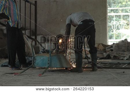 Abetifi, Ghana: July 27th 2016 - Sparks Flying As Man Welds Wheelbarrow Wheel In Abetifi, Ghana