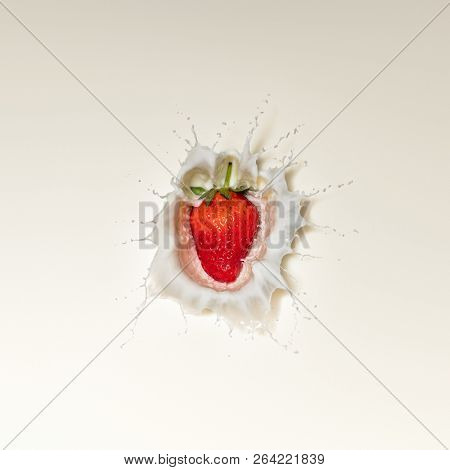 Fresh Red Strawberry fruit splash in white milk and viewed directly from above