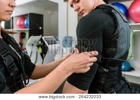 Woman fastening electro muscular stimulation vest on man poster
