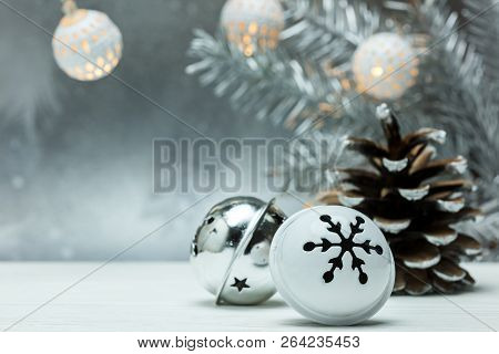 Silver Pine Cone And Christmas Jingle Bells On Gray Blurred Background With Fir Tree Branch And Garl