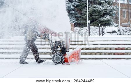 Snow-removal Work With A Snow Blower. Man Removing Snow. Heavy Precipitation And Snow Piles
