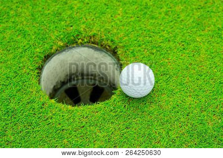 Golf Ball On Lip Of Cup, Golf Ball And Golf Hole On Green Grass.