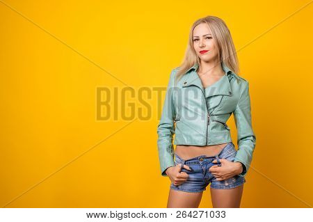Sexy Young Girl In Leather Jacket And Short Denim Shorts On A Yellow Background