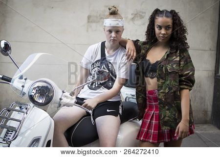 Teenagers Pose On A Moped. One Wears A Short Red Checkered Skirt And Top. The Second Wears Sports Sh