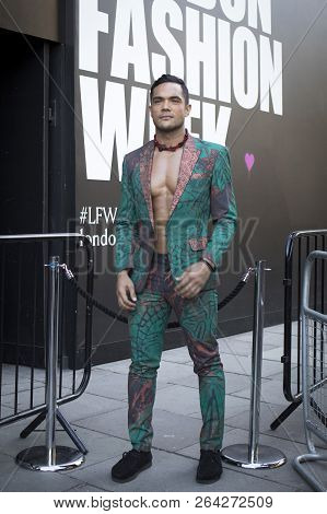 A Man In A Green Suit With Flowers From Armani