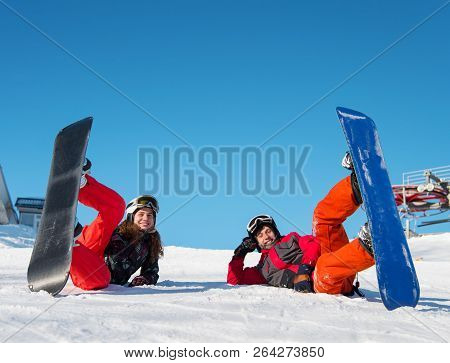 Pair Lying With Their Snowboards On Ski Slope And Looking At The Camera With Smile On The Background
