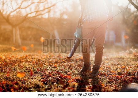 Close Up Details, Portrait Of Gardener Using Leaf Blower And Vacuum. Autumn Clean Up