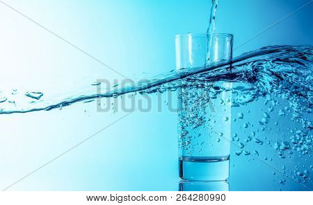 Blue Water Splash Pours Into A Glass On A Beautiful Blue Sea Wave Background. Glass Of Clean Drinkin