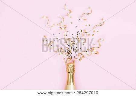 Champagne Bottle With Confetti Stars And Party Streamers On Pink Background. Christmas, Birthday Or