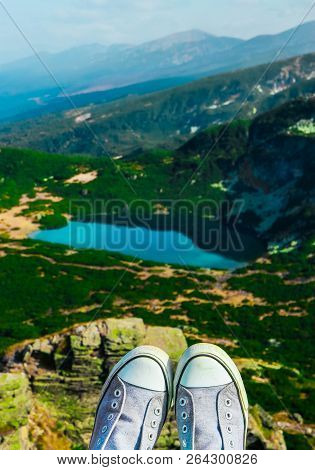 Alpine Mountain Lake, Green Meadows, Hiking Trail. Amazing Valley Landscape. Hiker Feet In Boots Han