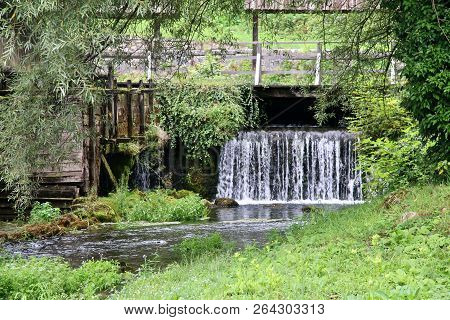 Babbling Brook And Stream Under A Wooden Bridge In The Countryside