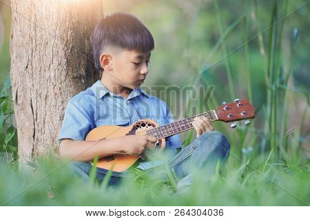 Adorable Boy With Guitar Sitting On The Grass On Sunset, Musical Concept With Little Boy Playing Uku