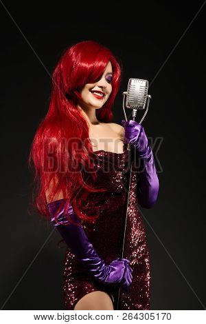 Young Smile Redhead Woman With Very Long Hair In Red Gown With Microphone On The Stand On A Black Ba