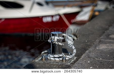 Close Up Of Tied Rope Of Boat On Concrete Dock On Sea