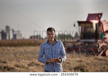 Handsome Farmer Standing In Soybean Field With Tablet While Combine Harvester Working In Background