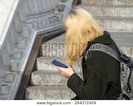 Blonde Girl With A Backpack Sitting With A Smartphone In Hands On The Street. Concept For Social Net