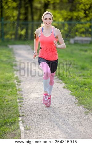 Young Woman Running In The Park On A Sunny Day